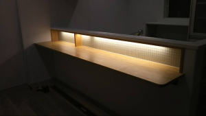 キッチンカウンター前です。ガラスタイルを間接照明で照らして幻想的な世界を演出